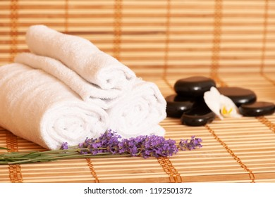 White towels and massage rocks in spa salon over dark and light bamboo background .