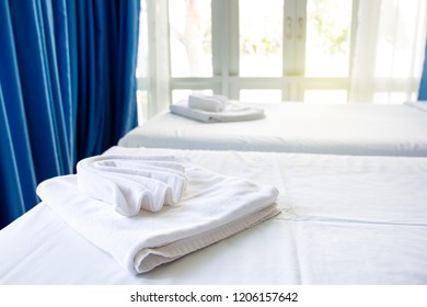 White towels on bed in hotel with garden view in background.