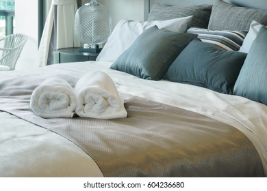 White towels on bed in stylish bedroom interior