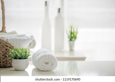 White towels on white table with copy space on blurred bathroom background. For product display montage.