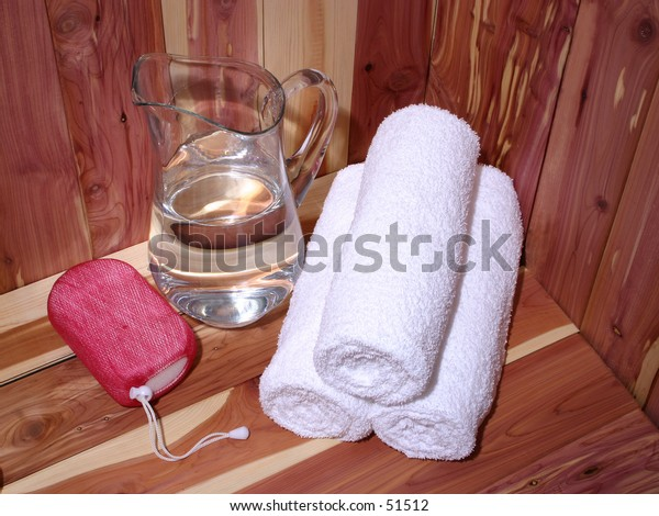 White towels, pitcher of water and body scrub on a cedar bench.