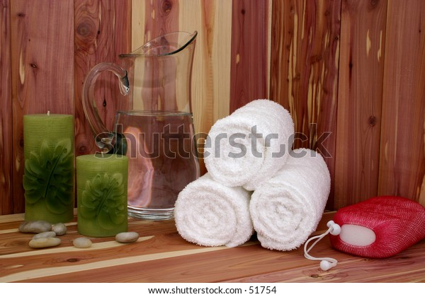 White towels, pitcher of water, candles, stones & body scrub on a cedar bench.