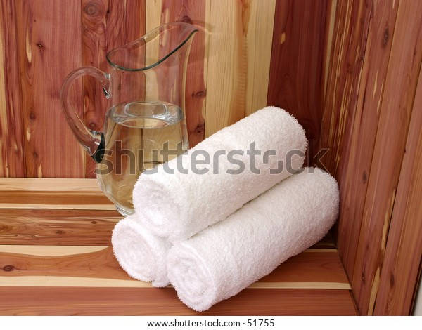 White towels and pitcher of water on a cedar bench.