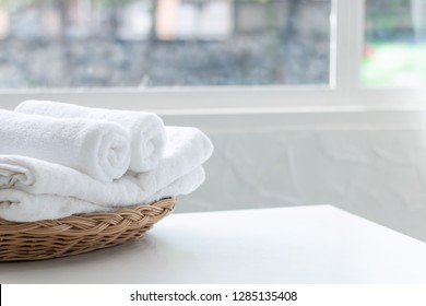 White towels in rattan basket on table with copy space blurred bathroom background.