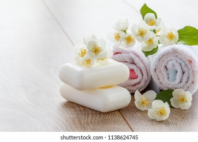 White towels and soap for bathroom procedures with flowers of jasmine on wooden boards with copy space. Spa products and accessories