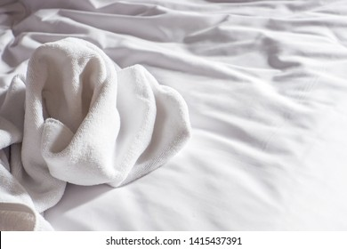 White towels used on the bed in the hotel room.
