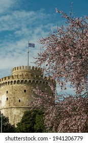The White Tower landmark in Thessaloniki with Greek flag waving on top on a spring day with cherry blossom trees visible.