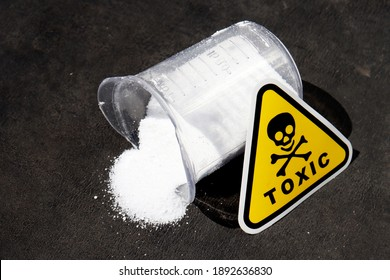 white toxic powder on a black background. a handful of toxic powder. toxic washing powder