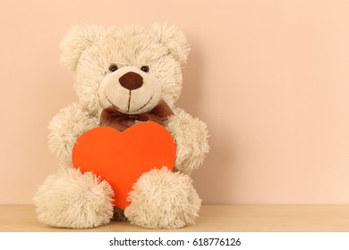 White toy bear Teddy with a red heart on a light pink background. Left side.