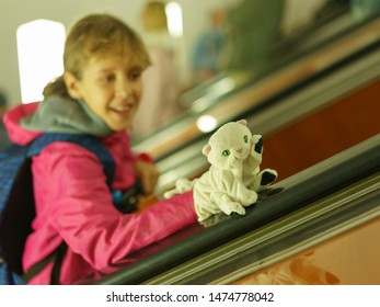 White toy kitten on the handrail in the subway. The child plays everywhere. It's suitable for greeting card design, postcard template.
