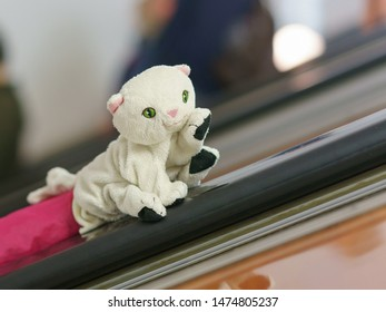 White toy kitten on the handrail in the subway. Child plays in the metro. It's suitable for greeting card design, postcard template.