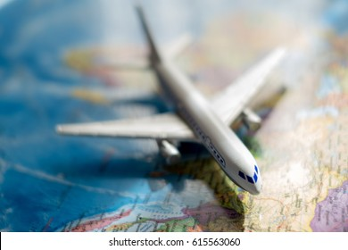 the white toy plane on the world map