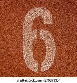 White track number on red rubber racetrack. textured running race tracks in outdoor stadium.