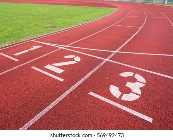 White track number on red rubber racetrack, texture of running racetracks in small stadium. Number one and number two. Outdoor exercise.