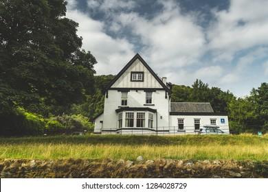White traditional Irish house among trees and fields. Northern Ireland. Stunning ethnic building among the wild nature environment. Amazing countryside landscape. Modern Irish architecture.