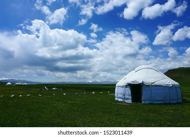 A white traditional nomadic yurt at the shore of Song Kol lake(3,016 m), Kyrgystan. Beautiful green pastures.