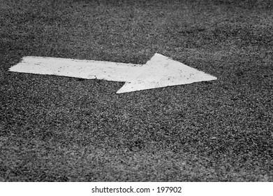 white traffic arrow on weathered asphalt
