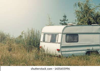 White trailer trailer house on wheels in the grass. Affordable Housing.