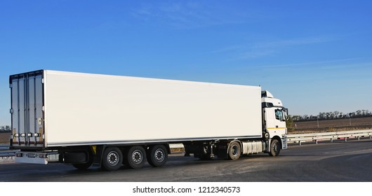 A white trailer on an asphalt road transports loads against the backdrop of the autumn landscape and plowed fields