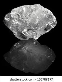 white transparent quartz stone macro with reflection on black background