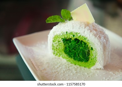 white tropical coconut cake with green pandan flavor on shredded coconut filling, topped  mint leaves and white chocolate, Asian sweet delight fruit snack dessert, summer food collection concept