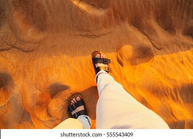 white trousers with legs and brown shoes step on desert