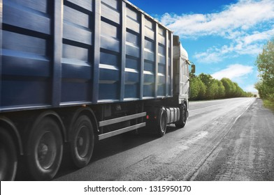 White truck with a blue container driving on the countryside road against blue sky with white clouds