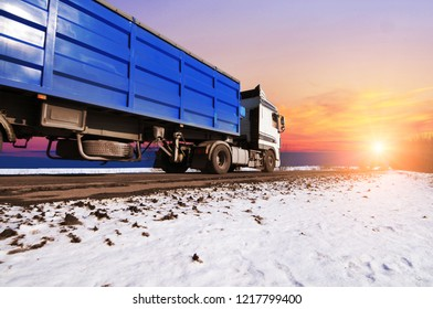 White truck and a blue trailer with on the winter countryside road with snow against night sky with sunset