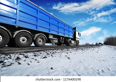 White truck and a blue trailer with space for text on the winter countryside road with snow against blue sky with clouds and bright sun
