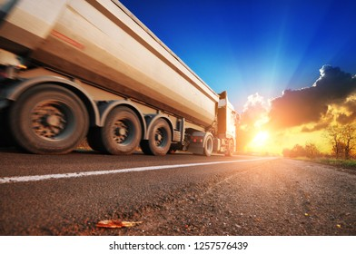 White truck with a container driving on the countryside road against night sky with sunset