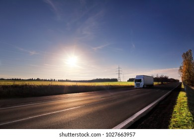 White truck driver on the road at sunset