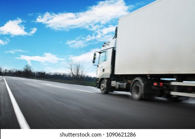 White truck driving fast and a white trailer with space for text on the countryside road against blue sky with clouds