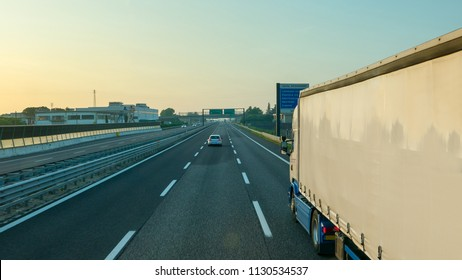 White truck driving motorway at sunrise, transportation background