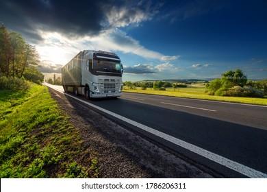Weißer Lastwagen auf Asphaltstraße in ländlicher Landschaft bei Sonnenuntergang mit dunkler Sturmwolke