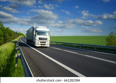 White truck driving on the asphalt road along the green fields and alleys in the countryside