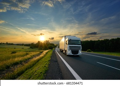 White truck driving on the asphalt road in rural landscape at sunset