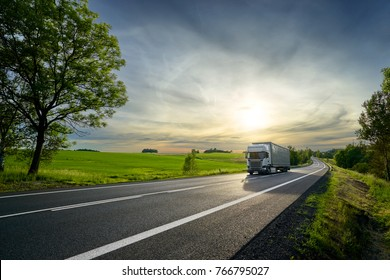 White truck driving on the asphalt road next to the green field in rural landscape at sunset