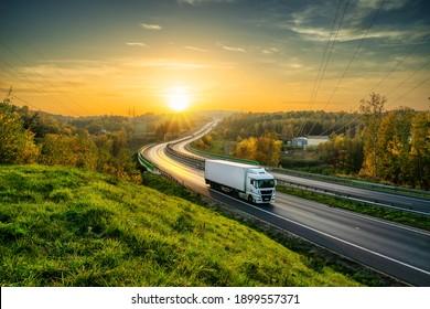 Weißer Lastwagen auf der Autobahn, die sich durch bewaldete Landschaft in Herbstfarben bei Sonnenuntergang zieht