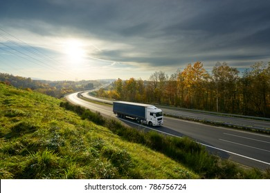 White truck driving on the highway turning towards the horizon in an autumn landscape with sun shining through the clouds in the sky