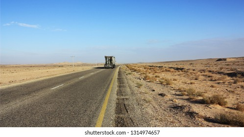 White truck goes to highway through scenic desert of Jordan. High voltage powerlines along asphalt road in arid valley. Early morning in wilderness after sunrise. Electric power poles. Horizontal.
