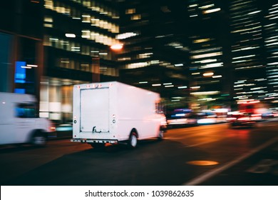 White truck of logistic shipping company on city road delivering goods for order quickly in time, truck moving speedily on avenue transporting and distributing stuff for postal service in metropolis