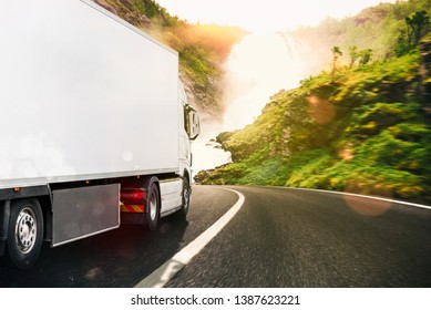 White truck moving on the road in a natural landscape at sunset