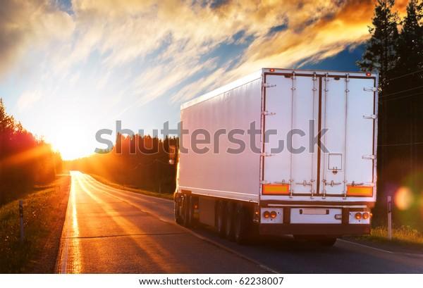 White truck on the asphalt rural road in the polar night