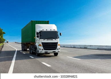 White Truck on highway road with green  container, transportation concept.,import,export logistic industrial Transporting Land transport on the asphalt expressway