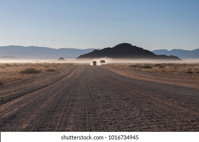 White truck on a road in the Namib desert in the morning mist, Namibia, Africa./White truck on a road in the Namib desert
