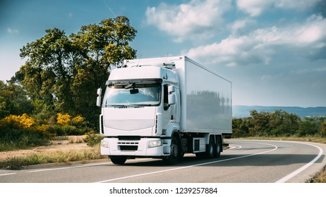 White Truck Or Traction Unit In Motion On Road, Freeway. Asphalt Motorway Highway Against Background Of Mountains Landscape. Business Transportation And Trucking Industry