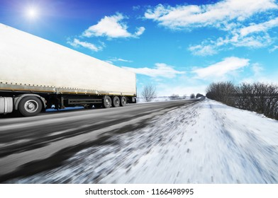 White truck and a white trailer with space for text driving fast on the winter countryside road with snow against blue sky with clouds and bright sun