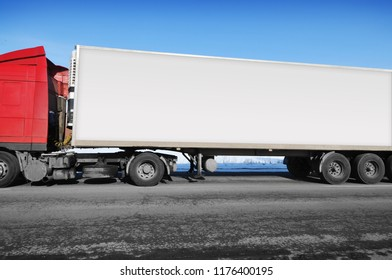 White truck and a white trailer with space for text on the winter countryside road with snow against blue sky