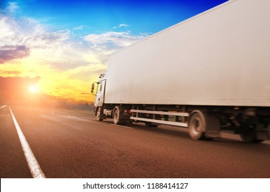 White truck and a white trailer with space for text on the countryside road against blue sky with bright sunset