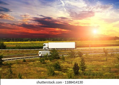 White truck with a white trailer and a van on the countryside road with fields and forest against night sky with sunset